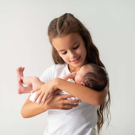 Little girl holding newborn baby sister in her arms. Cute children's portrait