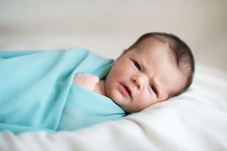 New born baby girl sleeps at home and smiling in a dream. Cute little kid's portrait Standard-Bild
