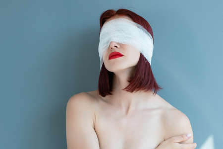 Bandaged eyes of young woman, conceptual indoor portrait. Person who doesn't notice anything. Patient after plastic or elective eye surgery. Girl with bandage on her head. Blind 写真素材