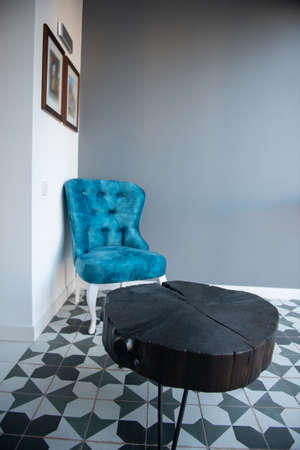 Modern design home interior with elegant blue chair in retro style and black wooden coffee table over gray wall. Stylish home decor