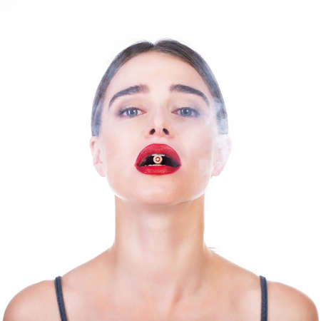 Beautiful young woman with red lipstick holding bullet in her teeth, smoke around.