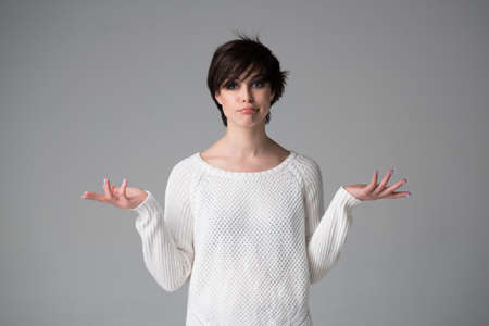 Beautiful young woman with nothing to do gesture and language of body to say apologies, regret, failure, fail, helplessness, studio shot over gray background