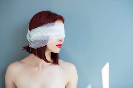 Bandaged eyes of young woman, conceptual portrait of person who doesn't notice anything. Patient after plastic or elective eye surgery.