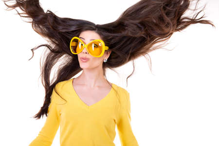 Happy smiling excited comical surprised young attractive woman with long flying hair and big funny yellow glasses isolated on white background. Imagens