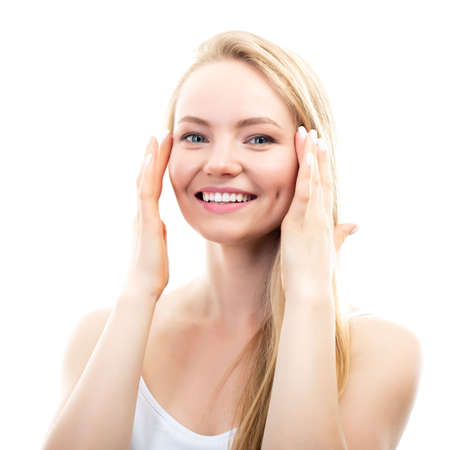 Happy smiling young beautiful blond woman touching her face, studio shot over white background. Beauty treatment, skin care, cosmetology concept