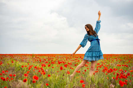 Young beautiful woman on a poppy field, summer outdoor.