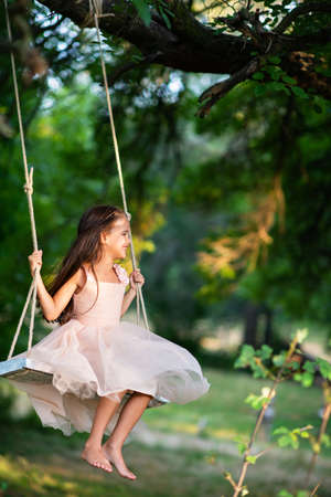 Happy girl rides on a swing in park. Little Princess has fun outdoor, summer nature outdoor. Childhood, child lifestyle, enjoyment, happiness.