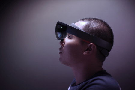 Portrait of young man with 3D virtual reality eye wear glasses hololens 1 in the lab