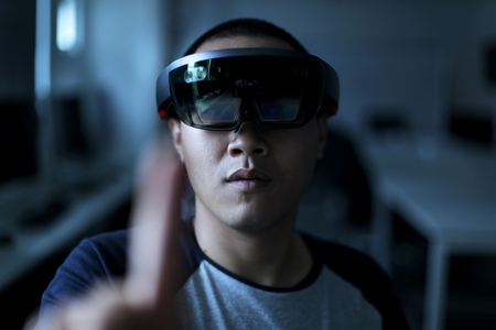 Portrait of young man with 3D virtual reality eye wear glasses hololens 1