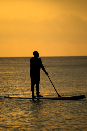 Silhouette man with the paddle sailing at sea