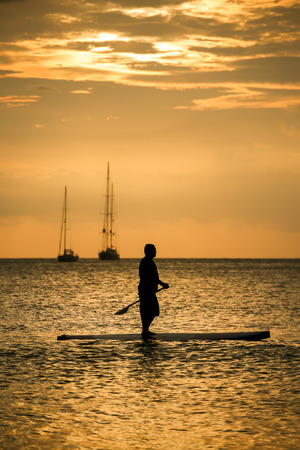 Silhouette Man with paddle on surfboard sunset moment Stock Photo