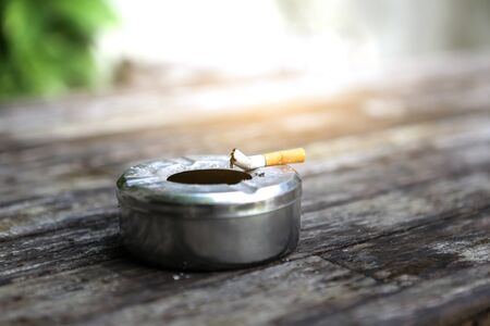 Metal ashtray with cigarette on wood table