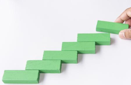 Concept de fondation de succès de construction. Main mettre des blocs de bois de puzzle rouge sous la forme d'un escalier ou faire un cadre photo.