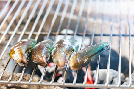 Mussels on the grill.Delicious festive barbecue on sand beach in the evening.Food and holiday concept.