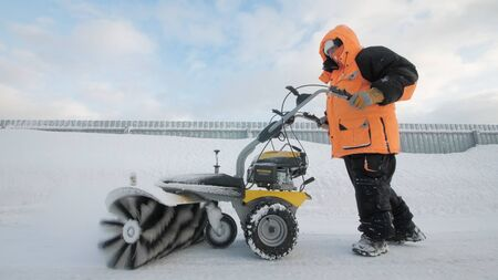 Man cleans snow in the yard with a sweeper in the winter