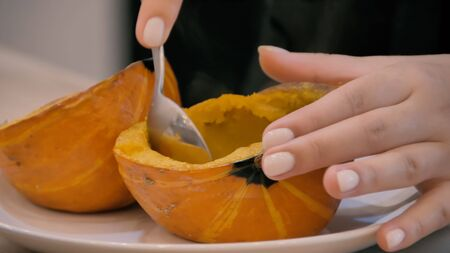 Girl picks boiled pumpkin with a spoon