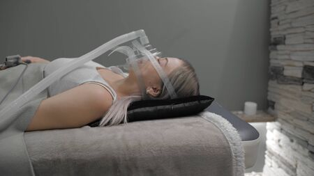 Girl lies on bed with artificial respiration mask