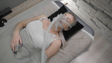 Young blonde girl lies on a bed connected to sensors with an unconscious lung ventilation mask. Foto de archivo