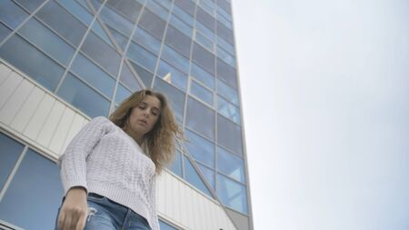 Girl in a white sweater with a sad look stands on the background of a business building
