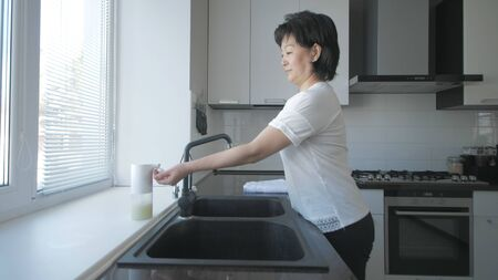 Asian woman washes hands with soap in the kitchen 免版税图像