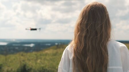 Girl in a white shirt and long hair stands with his back and a flying drone in the background
