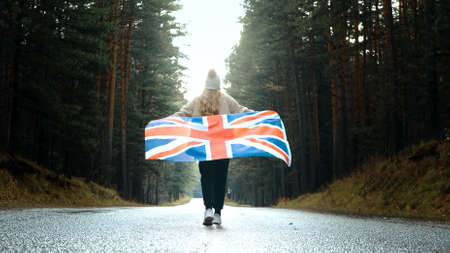 Girl walking on the road with the flag of United Kingdom