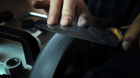 Man sharpens knives on a grinder. Close up hand