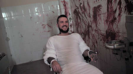 Crazy man in straitjacket tied to a chair, killer psychopath in a room smiles with bloodied walls overdose