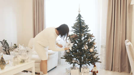 Pretty attractive woman in a dress decorates the Christmas tree with balls and Christmas decorations celebrating the New Year at home