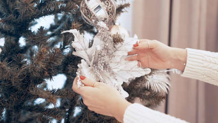 Female hands decorate christmas tree with toys at home