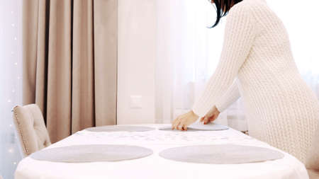 A girl in a white dress serves plate coasters on the table Banco de Imagens