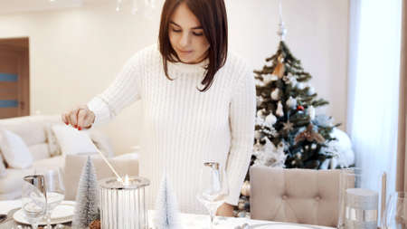 A girl in a white dress lights a candle at the Christmas table. Festive table setting