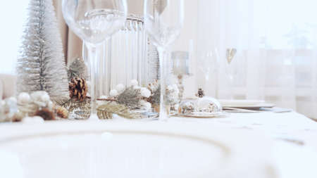 A girl in a white dress serves carnival at the Christmas table. Festive table setting