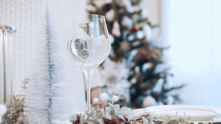 A girl in a white dress pours white wine into a glass. Christmas beautiful canned table