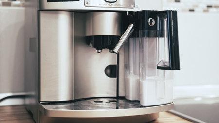 Womans hand puts a glass into the coffee machine Banco de Imagens