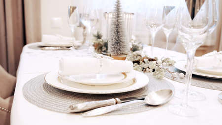 The girl with red nails removed the festive napkin from the plate. Christmas table setting Banco de Imagens