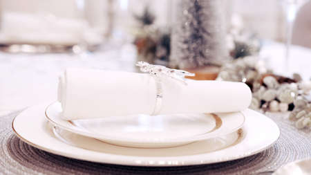 The girl with red nails put the festive napkin on the plates. Christmas table setting Banco de Imagens