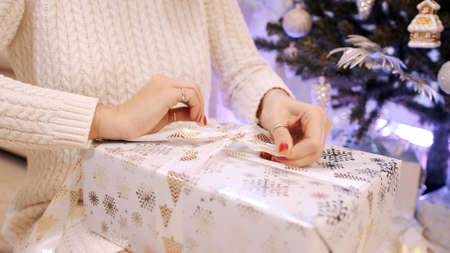 Beautiful brunette with a white dress opens a gift box from under the Christmas tree