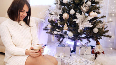 Young brunette girl with white dress sits with coffee and looks at the christmas tree