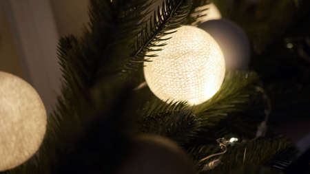 Beautiful light-colored toys hang on the Christmas tree at home. cedar cone. night