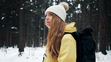 Girl with a white hat in the forest with a backpack in winter. Side view. Close up