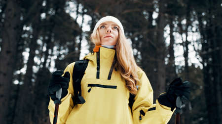Girl with a white hat in the forest with a backpack and hiking sticks in winter. Front view. Close up