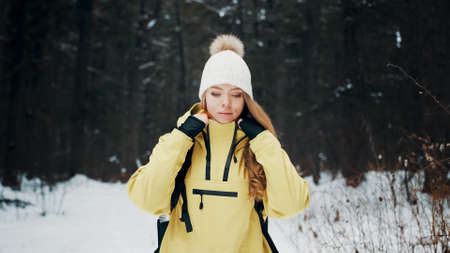 Girl with a white hat in the forest with a backpack in winter straightens his jacket. Front view