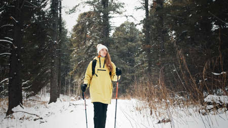 Girl with a white hat in the forest with a backpack and hiking sticks in winter. Front view Banco de Imagens