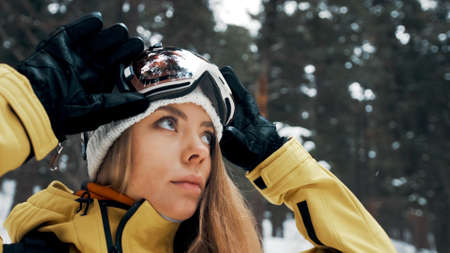 Girl with a white hat and snowboard mask in the forest in winter. Side view. Close up Banco de Imagens