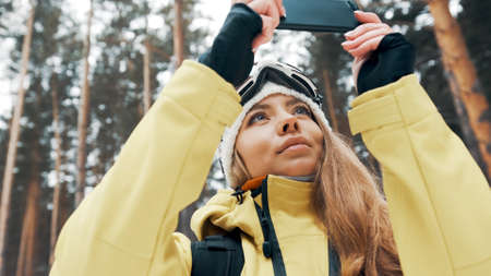 A girl in a white hat and a snowboard mask in the forest photographs nature on the phone in winter Banco de Imagens