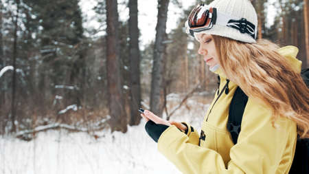 The girl leafs through photos on the phone in the forest in winter Banco de Imagens