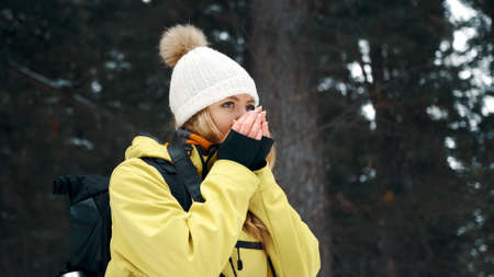 A girl in a white hat and a yellow anorak warms her hands in the winter in the forest