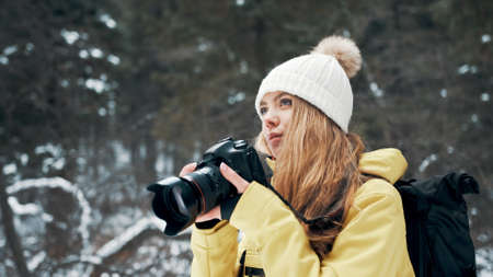 A girl with a backpack and a yellow anorak photographs the landscape on a professional camera Banco de Imagens