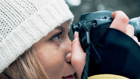 The face of the girl from the side leans the camera to the face in the winter in the forest
